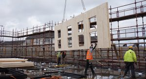 four workmen installing a clt wall with scaffolding in the background