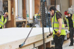 three men in hi viz tops working on a timber panel on chains in a factory